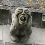 gargoyle with hands over eyes